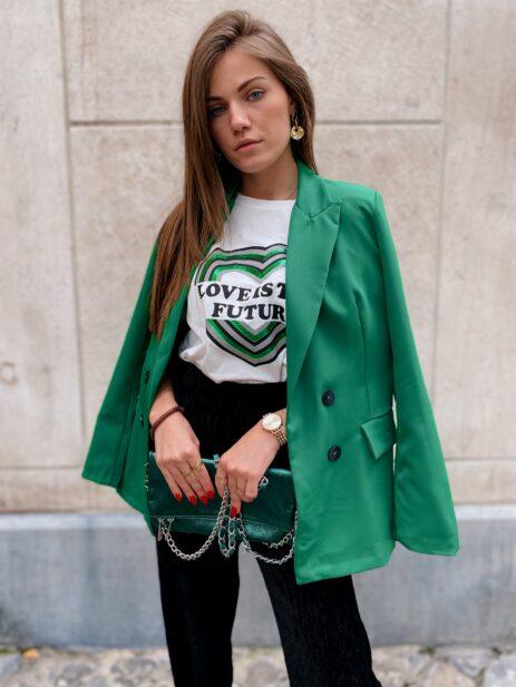 Blazer vert porté avec un pantalon noir et un t-shirt à motif coeur