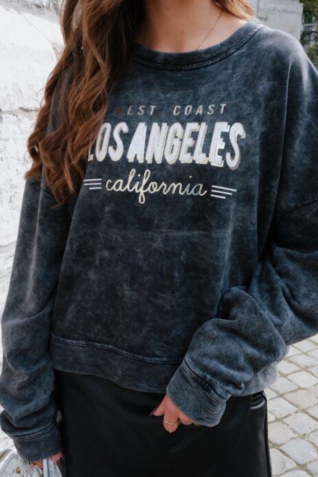 Sweat gris avec inscription Los Angeles rentré dans une jupe simili noire détails